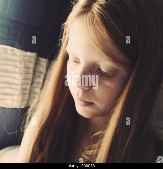 A young girl looks down while sunlight lights up one side of her face - Stock Image