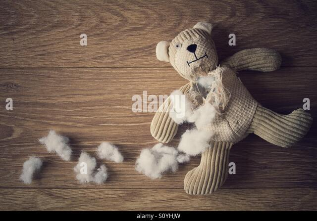 A small teddy bear laying on a wooden floor with his stuffing torn and pulled out. - Stock Image