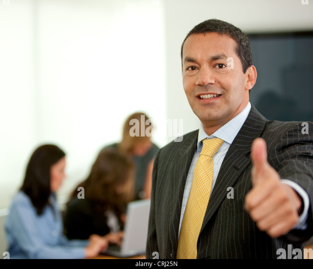 business man with thumb up and people in the background working at a laptop - Stock Image