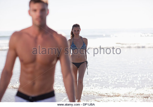 Couple playing in waves on beach - Stock Image