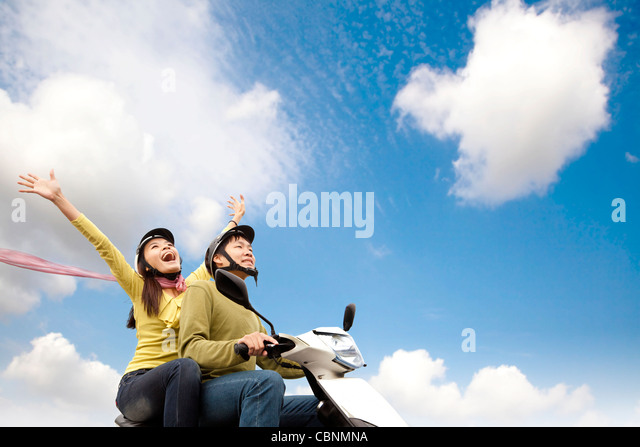 Happy young couple having fun on a scooter - Stock Image