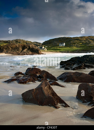 Waves roll in onto the shore during high tide at the remote and picturesque Clachtoll Bay. - Stock-Bilder