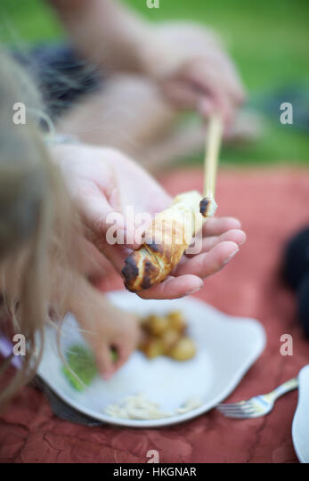 mans hand serving a homemade campfire bread to a child - Stock Image