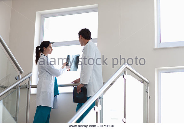 Doctors reviewing x-ray on stairs - Stock Image