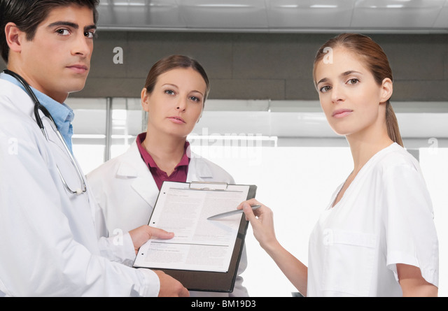 Three doctors with a medical report - Stock Image