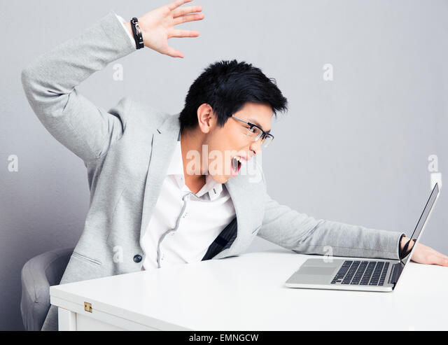 Angry young businessman in glasses sitting at the table with laptop over gray background - Stock Image