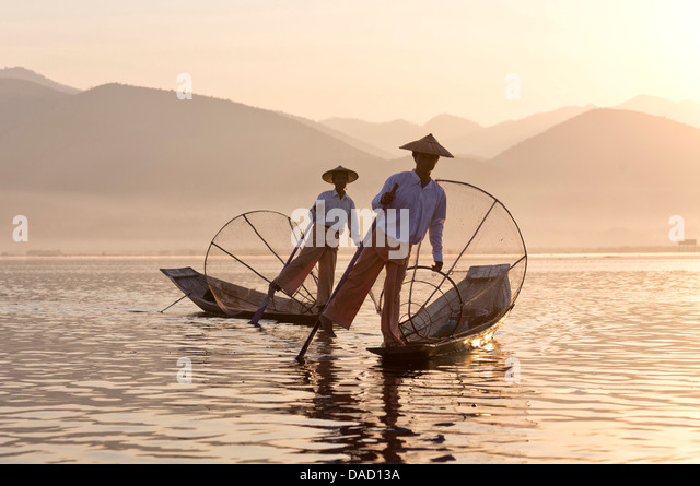 Intha 'leg rowing' fishermen at sunset on Inle Lake, Inle Lake, Myanmar - Stock Image