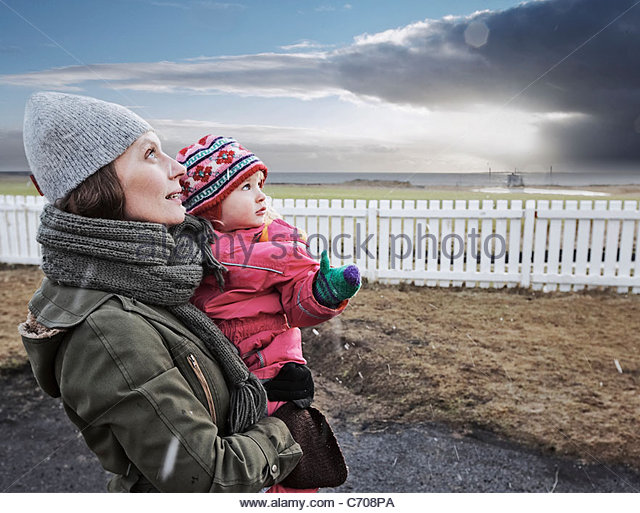 Mother and daughter watching sky - Stock Image