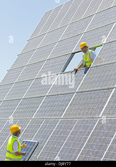 Workers examining solar panels - Stock Image