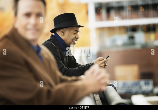 Professional people on the go keeping in contact using mobile phones Two men in coats leaning on a railing - Stock Image