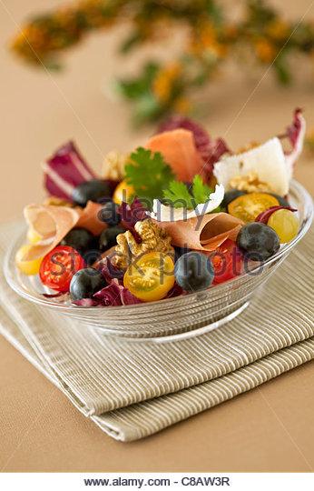 Cherry tomato,black olive and raw ham salad - Stock Image