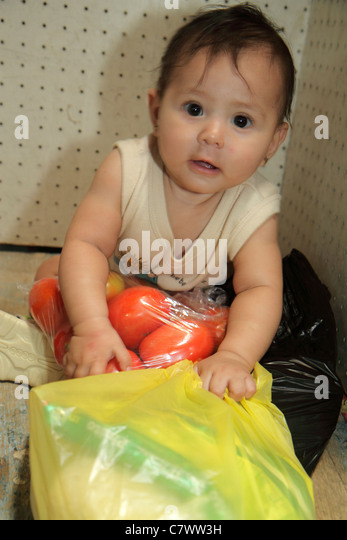 Managua Nicaragua Mercado Roberto Huembes market shopping Hispanic baby sitting playing holding plastic bag tomatoes - Stock Image