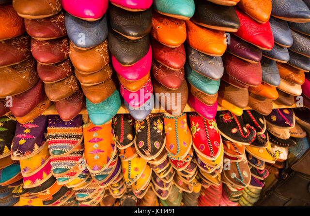 Hand-made leather slippers in many bright colours line the walls of a shop attached to a tannery in Fez, Morocco. - Stock Image