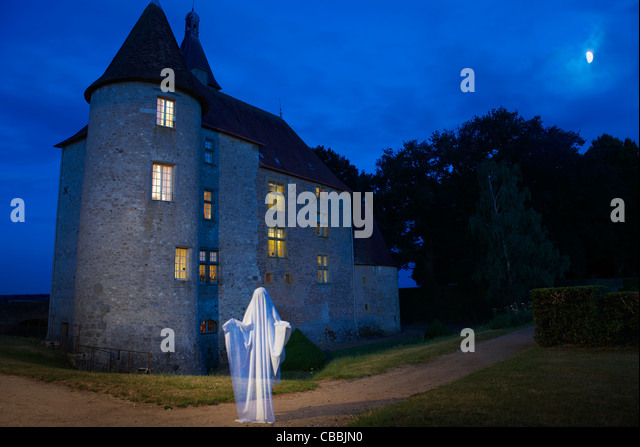 Ghost floating outside stone house - Stock Image