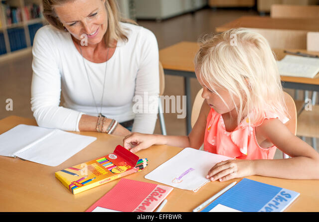 Teacher watching girl drawing with color pencils in classroom - Stock Image