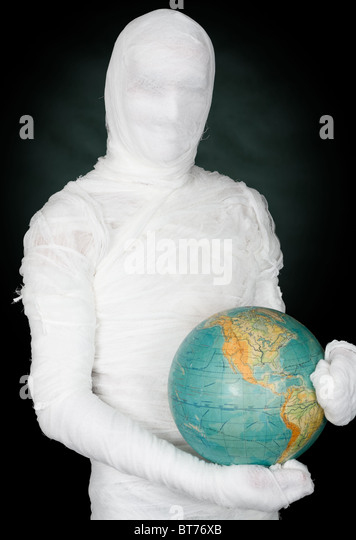 Man in costume mummy and terrestrial globe on black - Stock Image