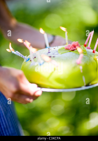 Woman holding birthday cake with lit candles, close-up - Stock Image