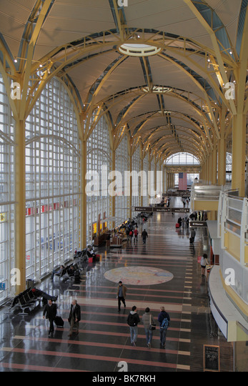 Virginia Arlington Ronald Reagan Washington National Airport DCA terminal main hall glass windows man traveler luggage - Stock Image