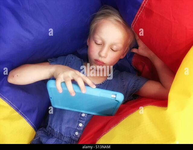 A child relaxes on a deflating primary-coloured ball to play with a mobile device. - Stock Image