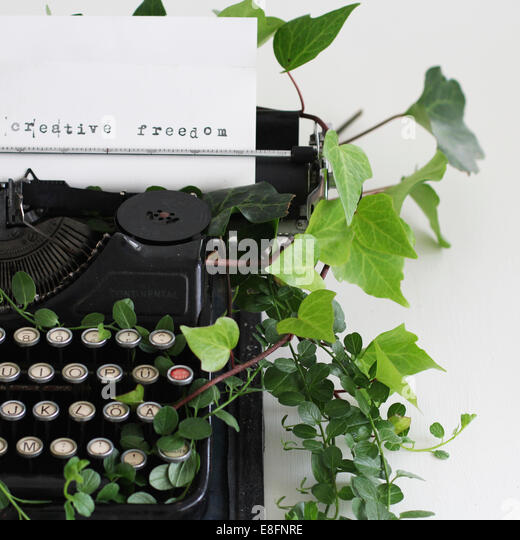 Creative Freedom typed on paper in typewriter surrounded by ivy - Stock Image