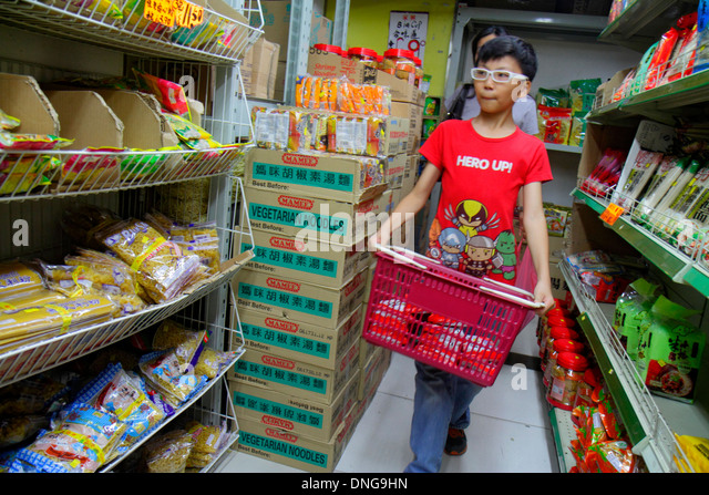 Hong Kong China Kowloon Sham Shui Po shopping grocery store supermarket sale display shelves Asian boy carrying - Stock Image