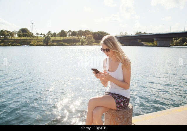 Young woman sitting at riverside texting on smartphone, Danube Island, Vienna, Austria - Stock Image