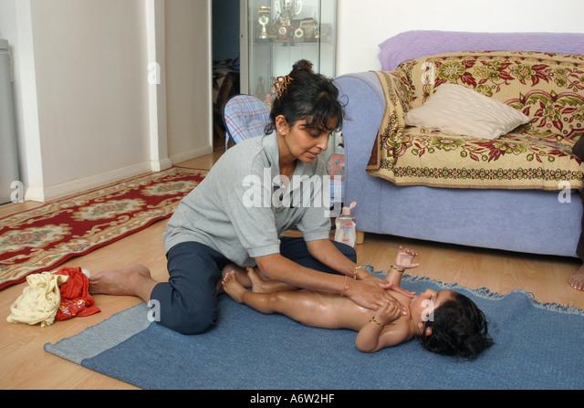 mother massaging baby oil into the baby's skin - Stock-Bilder