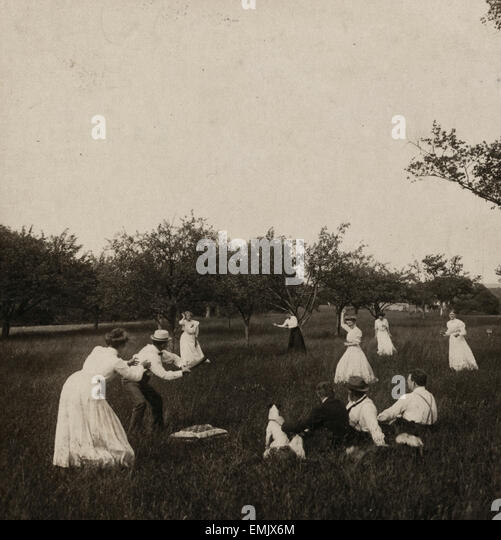 Playing baseball at Madison, New Jersey  Photograph shows women and men playing baseball in a field of tall grass. - Stock Image