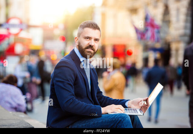 Hipster manager working on laptop on sunny Piccadilly Circus, Lo - Stock Image