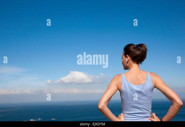 Back View of Woman Wearing Earbuds Looking at the Ocean - Stock Image