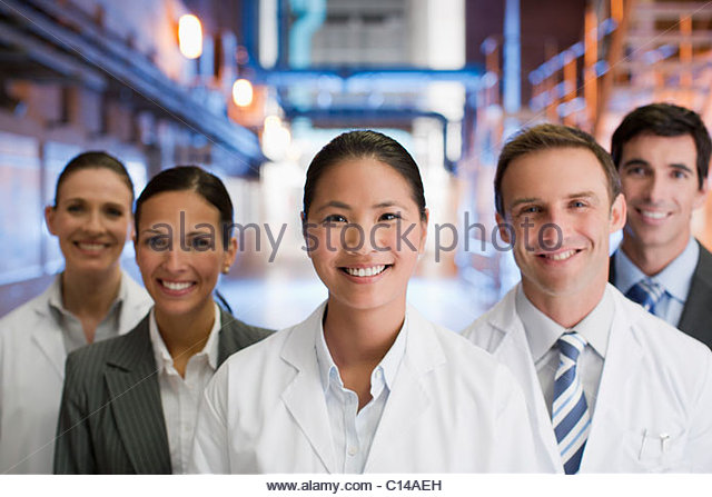 Business people and scientists standing together in factory - Stock-Bilder
