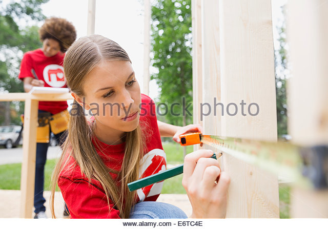 Volunteer measuring construction frame with tape measure - Stock Image
