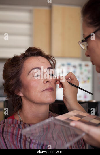 Mature woman having make-up applied by make-up artist - Stock Image