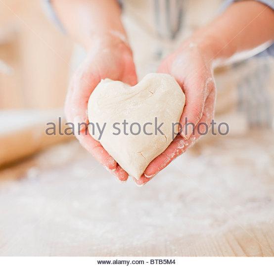 Close up of woman holding heart-shape dough - Stock-Bilder