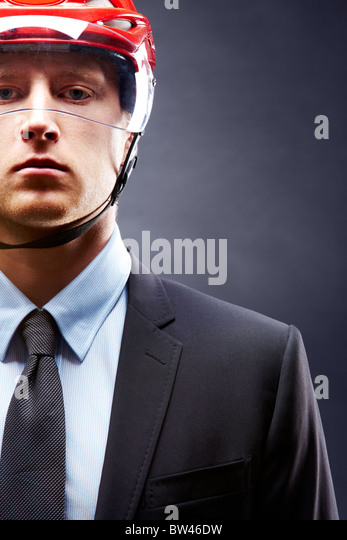 Portrait of young businessman with hockey helmet on head - Stock Image