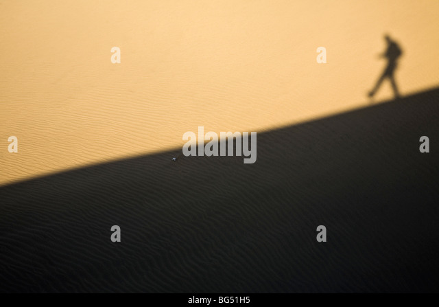 Shadow of a man walking down a sand dune - Stock Image