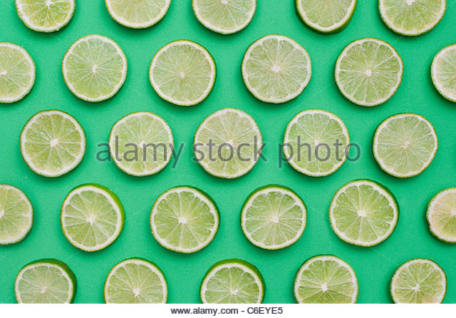 Citrus x sinensis. Lime fruit slices on green background . Food pattern - Stock Image