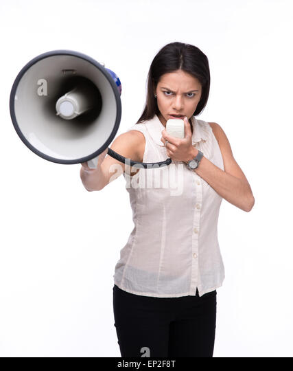 Angry businesswoman standing with megaphone over white background and looking at camera - Stock Image