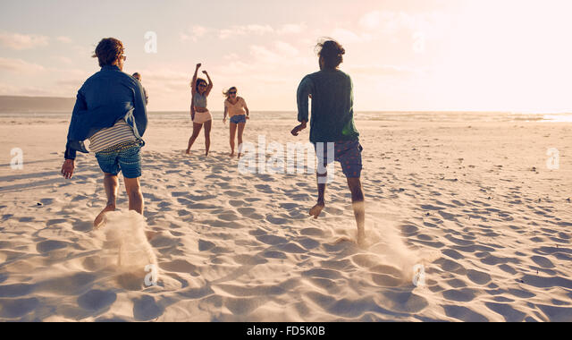 Group of young people running and competing together on a sandy beach. Young men running a race on the beach. - Stock Image