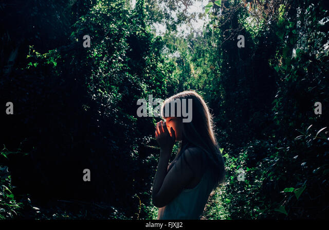 Side View Of Young Woman Against Trees In Forest - Stock-Bilder