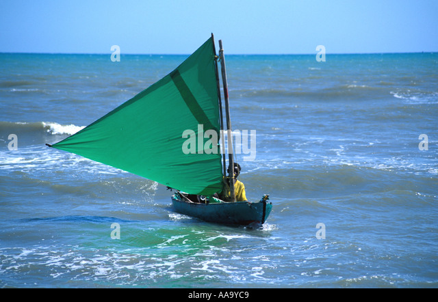 Honduras Garifuna fisherman wooden dugout canoe with sail Caribbean coast Central America Horizontal - Stock Image