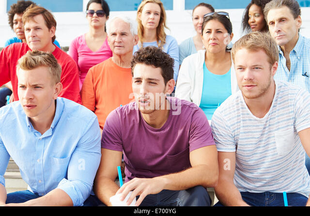 Crowd Of Spectators Watching Outdoor Sports Event - Stock Image