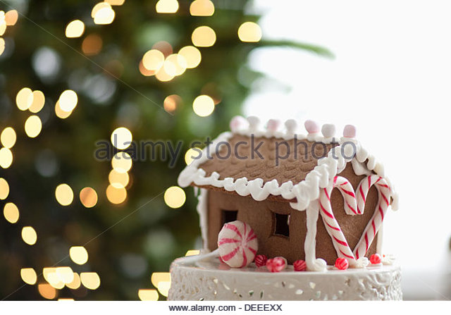 Gingerbread house in front of Christmas tree - Stock Image