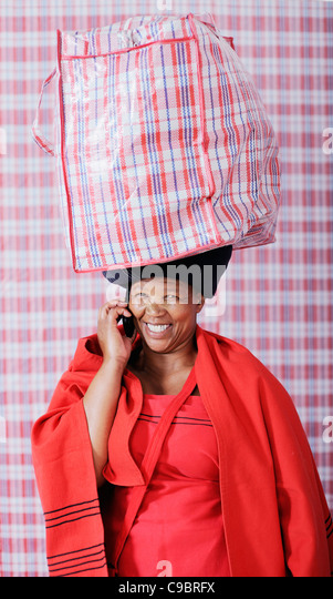Woman in traditional outfit carrying bag on using mobile phone, Cape Town, Western Cape Province, South Africa - Stock Image