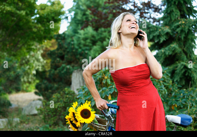 Woman talking on cell phone on bicycle - Stock-Bilder