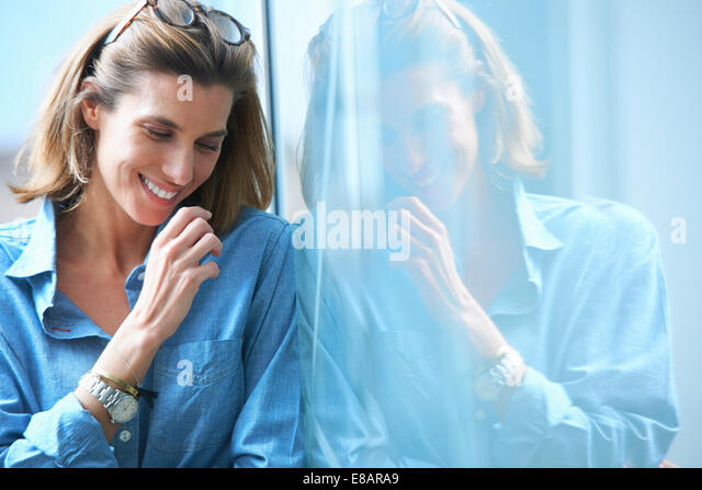 Candid shot of mid adult businesswoman leaning against glass wall in office - Stock Image