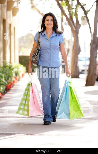 Hispanic woman carrying shopping - Stock Image