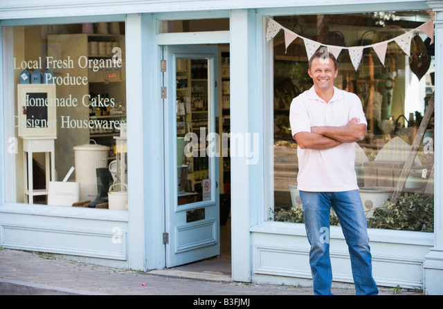 Man standing in front of organic food store smiling - Stock Image