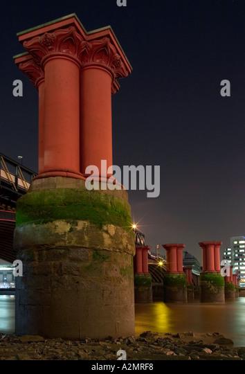 Columns of disused Blackfriars Rail Bridge at night. Thames foreshore, London, England - Stock Image