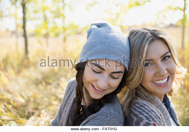Portrait smiling women back to back - Stock Image